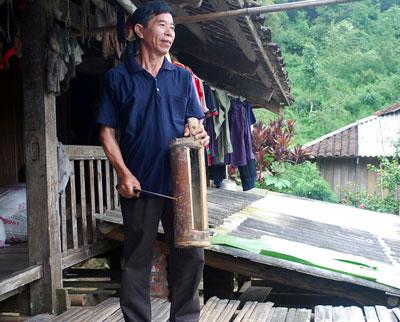 Trưởng thôn Khâu Đấng dùng mõ tre tập hợp người dân khi có việc cần